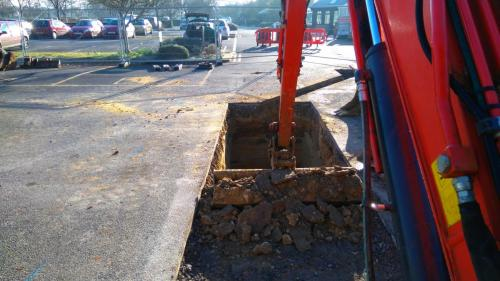 Opening up the ground in the car park of large garden centre for foul drainage installation